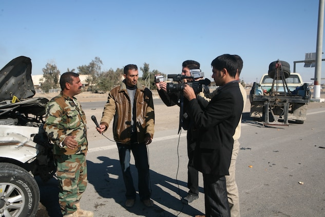 News crews interview Iraqi policemen with the Karmah police Station after a suicide attack on a local highway in Fallujah, Iraq, Dec. 28. Iraqi Security Forces were quick to respond to the situation and provided casualty assistance to injured personnel.