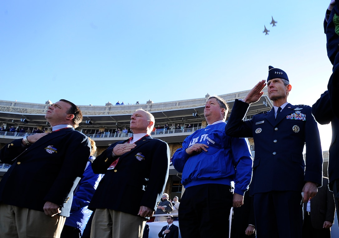 Secretary of the Air Force Micheal B. Donley (center) and Air Force Chief of Staff Gen. Norton A. Schwartz (right) salute during the national anthem while F-16 Fighting Falcons from the 301st Fighter Wing perform a fly-over before the Bell Helicopter Armed Forces Bowl game between the U.S. Air Force Academy and the University of Houston on Dec. 31 at Fort Worth, Texas. (U.S. Air Force photo/Staff Sgt. Bennie J. Davis III)