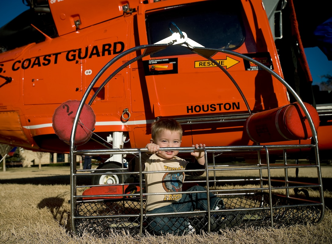 Gavin Sanchez, 2, sits in the rescue basket of a MH-65 Dolphin at a U.S. Coast Guard exhibit during the Adventure Day celebration and pep rally Dec. 30 for the Bell Helicopter Armed Forces Bowl game at Amon G. Carter Stadium in Fort Worth, Texas.  (U.S. Air Force photo/Staff Sgt. Bennie J. Davis III)