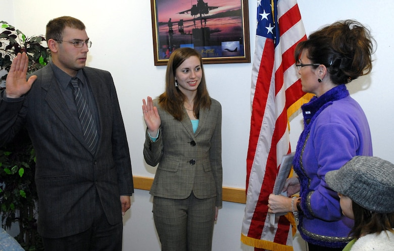 Alaska Governor Sarah Palin, commander-in-chief of the Alaska Air National Guard, administers the military Oath of Enlistment to Justin Lawson and his sister, Jessica Newton, at the opening of the guard's new Valley Recruiting Office Dec. 22, 2008. A joint venture between the Alaska National Guard and the active-duty Air Force, the office is the Guard's first-ever full-time presence in the Mat-Su Valley. Alaska National Guard photo by 2nd Lt. John Callahan.