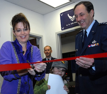 Alaska Governor Sarah Palin, commander-in-chief of the Alaska Air National Guard, cuts the ribbon at the opening of the guard's new Valley Recruiting Office Dec. 22, 2008, while daughter Piper, 7, looks on. A joint venture between the Alaska National Guard and the active-duty Air Force, the new office is the guard's first-ever full-time presence in the Mat-Su Valley. Assisting the governor is Lt. Gen. (Alaska) Craig Campbell, adjutant general of the Alaska National Guard. In the background is Maj. Ed Soto, commander of the 176th Wing's Civil Engineer Squadron. Alaska National Guard photo by 2nd Lt. John Callahan.