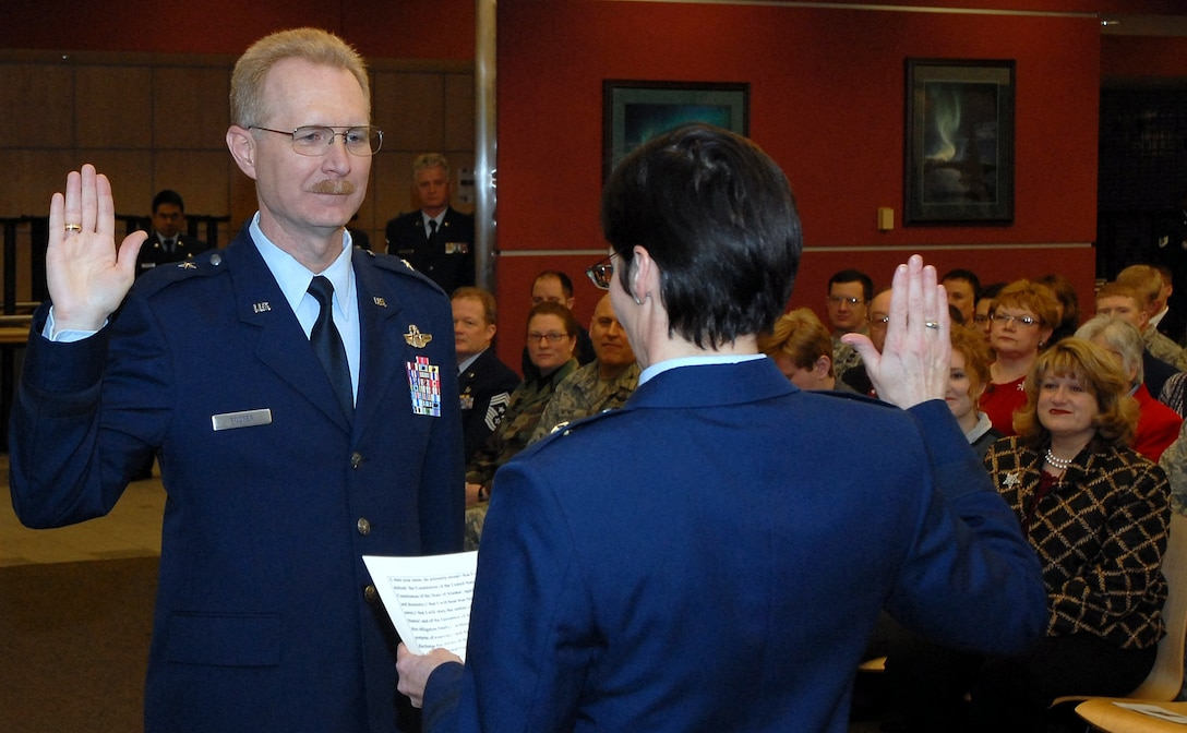 "Brig. Gen. Deborah McManus, Alaska's assistant adjutant general for air, administers the military oath of office to newly promoted Brig. Gen. Charles E. ""Chuck"" Foster Jr. before a packed house at Kulis Air National Guard Base Dec. 18. A former rescue helicopter pilot, Foster assumed command of the 176th Wing in July. He is the unit?s 16th commanding officer and the fourth to be promoted to general officer. Alaska Air National Guard photo by 2nd Lt. John Callahan."