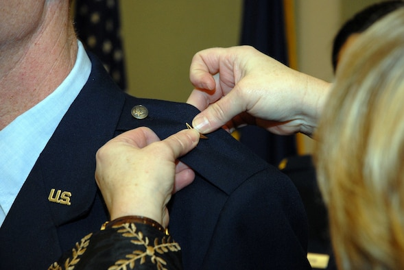 """Julie Foster, wife of newly promoted Brig. Gen. Charles E. """"Chuck"""" Foster, pins on one of the new general's stars at a promotion ceremony held Dec. 18 before a packed house at Kulis Air National Guard Base. As a commander's spouse, Julie plays an important role in the wing's family support programs. Alaska Air National Guard photo by 2nd Lt. John Callahan"""