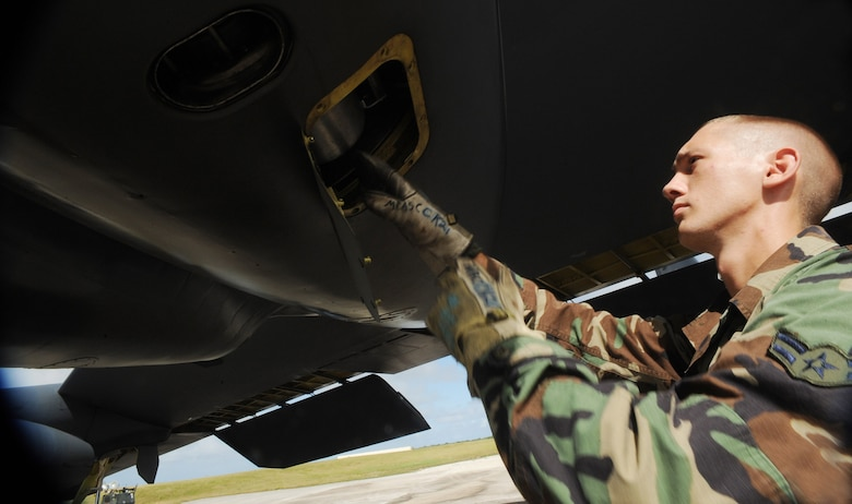 "Airman 1st Class Michael Brand, 36th Expeditionary Aircraft Maintenance Squadron crew chief, loads a ""quick start"" cartridge on a B-52 Stratofortress before a local training mission Dec. 30 at Andersen Air Force Base, Guam. Throughout the month of December, deployed Airmen have been launching aircraft by a method known as cartridge starts, or ""Cart-Starts."" During these launches, a small-controlled explosive is inserted into two of the eight engines located on the B-52 providing a rapid response launch capability. Airman Brand is deployed from Minot AFB, N.D. (U.S. Air Force photo/Master Sgt. Kevin J. Gruenwald)"