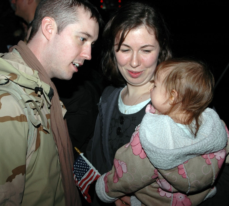 NIAGARA FALLS AIR RESERVE STATION, N.Y. -- Staff Sgt. John Glyshaw, 914th Security Forces Squadron, greets his wife and daughter on the flight line here after stepping off the C-130 aircraft that brought him home Jan. 29 from deployment to Iraq. (U.S. Air Force Photo / Airman Andrew Caya)