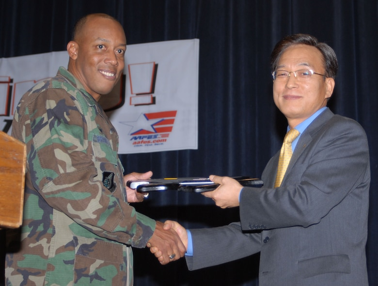 """KUNSAN AIR BASE, South Korea -- Col. C.Q. """"Wolf"""" Brown, 8th Fighter Wing commander presents Mr. Jung, Soo-hyun, COO Hyundai Engineering with a plaque as a token of appreciation for Hyundai Engineering's dedication to the new theater project during the theater grand opening here Feb. 1.  The new theater has 200 more seats than the previous theater that was built in 1962.  The increase in capacity will enable the Wolf Pack to accept follow on forces more efficiently.  (U.S. Air Force photo/Staff Sgt. Darcie Ibidapo)"""