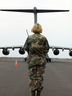 Master Sgt. Christina Bolle, an airfield manager with the 36th Contingency Response Group, Andersen Air Force Base, Guam, greets an arriving C-17 Globemaster III at the Kona International Airport, Kona, Hawaii, during an aeromedical transport mission Feb. 2.  The 36th CRG deployed more than 85 Airmen to Kona who set-up and provided base operational support including security, airfield management, water and power production, food services and a tent city capable of housing 300 during exercise Pacific Lifeline.  (U.S. Air Force Photo by Senior Master Sgt. Charles Ramey)