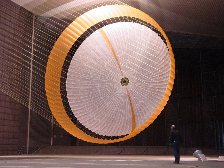 In this image, an engineer is dwarfed by NASA's Mars Science Laboratory's parachute, which holds more air than a 3,000-square-foot house and is designed to survive loads in excess of 36,000 kilograms (80,000 pounds). The parachute, built by Pioneer Aerospace, South Windsor, Conn., has 80 suspension lines, measures more than 65 feet in length, and opens to a diameter of nearly 55 feet. It is the largest disk-gap-band parachute ever built and is shown here inflated in the test section with only about 12.5 feet of clearance to both the floor and ceiling of the world's largest wind tunnel at National Full-Scale Aerodynamics Complex. The parachute is attached to a launch arm mounted on a swivel-base that allows the test item to pitch and yaw under simulated conditions of subsonic entry into the Martian atmosphere. (Photo courtesy of NASA/JPL and Pioneer Aerospace Corp.)