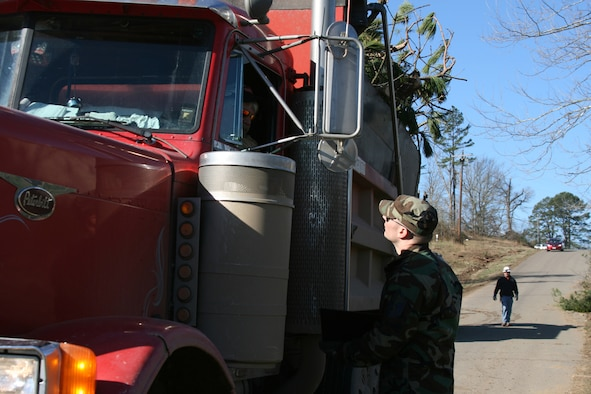 Master Sgt. Matthew Pfleger, an Arkanas Air National Guardsman with the 189th Airlift Wing, checks in a dump truck Feb. 9 full of debris headed to a burn pit in Clinton, Ark. Security forces members manned the entry-contol point to keep sightseers and looters out. An EF4 tornado, measured on the Enhanced Fujita scale, had winds of 166-200 mph as it ripped a 123-mile path through North Central Arkansas. About 50 Arkansas Army and Air National Guard Soldiers and Airmen are helping provide security in Clinton and Van Buren County. Arkansas National Guard officials expect them to be in the area for about a week. (U.S. Air Force Photo by Master Sgt. Bob Oldham)