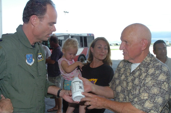 The 478th Expeditionary Operations Squadron commander, Lt.Col. Robert Leonard, accepts a bottle of children's vitamins to donate to Shekinah Orphanage from Bob Eredics, Vitamins for the World director. The Coast Guard, Air Force, Vitamins for the World and Extreme Response International worked together to bring over one million vitamins to less fortunate children and adults in Ecuador. (U.S. Air Force photo by Capt. Ashley Norris)