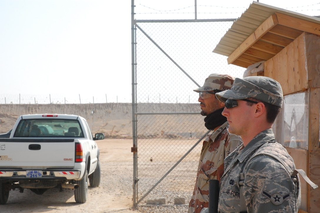 CAMP BUCCA, Iraq – Airman Mikel Whited, 886th Expeditionary Security Forces Squadron, and an Iraqi Correctional Officer stand guard outside the Theater Internment Facility in Camp Bucca, Iraq, Feb. 10, 2008.  Approximately 1,000 ICOs work side-by-side Airmen, Sailors and Soldiers guarding detainees at the TIF housing detainees determined to be a security threat against Iraqi citizens or coalition forces. Airman Whited is deployed from Eielson Air Force Base, Alaska. (U.S. Air Force Photo/Capt. Jason McCree)