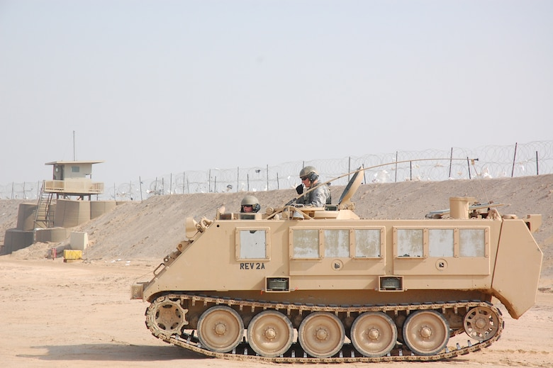 CAMP BUCCA, Iraq – Senior Airman Travis Hummel, standing, and Airman 1st Class Adam Giebitz patrol with a watch tower in the background, in an M-113 Armored Personnel Carrier at the Theater Internment Facility in Camp Bucca, Iraq, Feb. 10, 2008.  Airmen Hummel and Giebitz are deployed from Robins Air Force Base, Ga., and are assigned to the 886th Expeditionary Security Forces Squadron's quick response force.  The QRF responds to issues within the TIF in which a show of force or escalation of force is required beyond the capabilities for the TIF's guard force.  (U.S. Air Force Photo/Capt. Jason McCree)