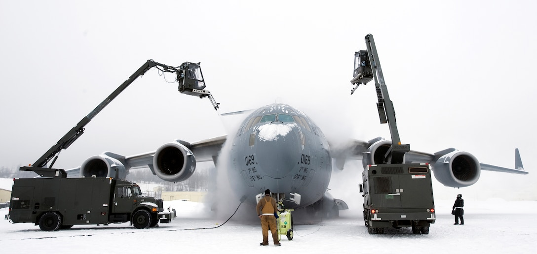 ELMENDORF AIR FORCE BASE, Alaska -- Members of the 703rd Aircraft Maintenance Squadron de-ice a C-17 Globemaster III from the 517th Airlift Squadron before a training mission. Heavy snow and weeks of sub-zero temperatures require extra effort from maintenance crews to keep the aircraft clear of ice and snow. The training mission included dropping Army Airborne Soldiers from Fort Richardson, Alaska, and conducting air drops of training bundles that simulate the Soldier's equipment. (U.S. Air Force photo by Master Sgt. Keith Brown)