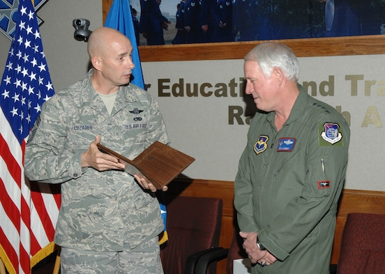 Chief Master Sgt. Mark Luzader, Air Education and Training Command command chief master sergeant, presents Gen. William R. Looney III, AETC commander, an invitation plaque Feb. 13 to receive the Order of the Sword at a ceremony May 30. (U.S. Air Force photo by Joel Martinez)