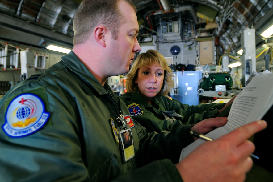 SCOTT AIR FORCE BASE, Ill. -- Capt. Mark Sprague, 375th Aeromedical Evacuation Squadron flight nurse, is briefed by Capt. Lisa Giugliano, 89th AES flight nurse, on patients before they are transferred to a C-130 aircraft Feb. 9 at Scott AFB, Ill. The 375th Airlift Wing located at Scott is one of three Aeromedical Staging Facility distribution hubs in the continental United States that is responsible for transporting patients to their home bases or other specialized hospitals. (U.S. Air Force photo/Master Sgt. Maurice Hessel)