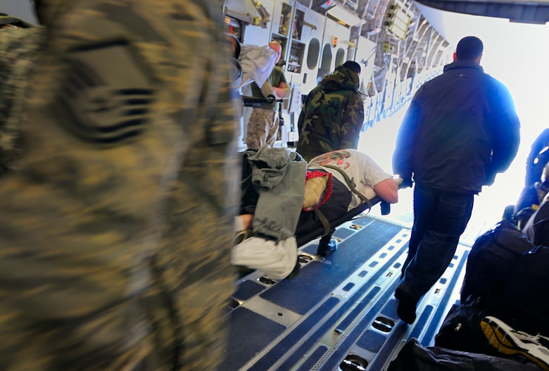 SCOTT AIR FORCE BASE, Ill. -- 375th Aeromedical Staging Facility medical technicians transfer a patient off a C-17 aircraft  to a C-130 or ASF room Feb.9 at Scott AFB, Ill. The 375th Airlift Wing located at Scott is one of three ASF distribution hubs in the continental United States that is responsible for transporting patients to their home bases or other specialized hospitals. (U.S. Air Force photo/Master Sgt. Maurice Hessel)