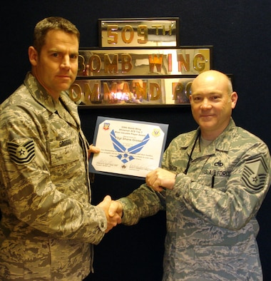 "WHITEMAN AFB - Tech. Sgt. Shane Grosso?s, 509th Bomb Wing Command Post, receives the Top III MVP award from Senior Master Sgt. Charles Davis, 509th Maintenance Squadron for February. Sergeant Grosso's training program has been lauded by both the Nuclear Surety Staff Assistance Visit and Air Combat Command Inspector General teams, stating that, ""CP training program is exceptional."" Unit training scenarios were called ""Best seen to date!"" His program has set the standard in ACC by being the 1st base out of 24 to have 100% of the Command Post pass the closed book exam.  He has also aided the 2nd and 5th Bomb Wing training managers; giving them tests and scenarios to increase their knowledge and emergency war order proficiency. (Courtesy Photo)"