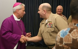 CAMP H.M. SMITH, Hawaii -- Most Reverend Joseph W. Estabrook, D.D., Auxiliary Bishop of Archdiocese of the Military Services, shakes hands with Col. James L. Stalnaker, Chief of Staff, U.S. Marine Corps Forces Pacific, after Roman Catholic mass, Feb. 15 in the chapel here.  The bishop intends to visit US troops and local churches throughout the region.  His intent is to better the partnership of the Roman Catholic churches.  He also wants to push youth programs in the region.