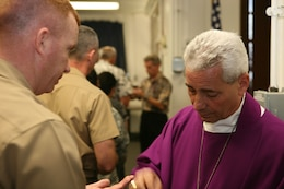 CAMP H.M. SMITH, Hawaii -- Most Reverend Joseph W. Estabrook, D.D., Auxiliary Bishop of the Archdiocese for the Military Services, offers Lt. Col. Andrew Regan communion during Roman Catholic mass, Feb. 15 in the chapel here.  The bishop met with chaplains and some commanders from each service to hear service members' concerns before beginning a Pacific-region tour.  He is scheduled to visit troops and local Roman Catholic churches in Singapore, Okinawa, Guam and Korea.