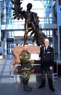DAYTON, Ohio -- Jerry Millhouse (right), a volunteer at the National Museum of the United States Air Force, accepts the Team Wright-Patt Volunteer of the Quarter award from 88th Air Base Wing Vice Commander Col. James H. Strickler. (U.S. Air Force photo)