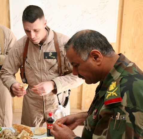 "Marine Col. Robert F. Castellvi,  1st Iraqi Army Division Military Transition Team senior adviser and commanding officer shares a meal with Maj. Gen. Tarik, commanding General 1st IA Div., Feb. 16, 2008  The meals was provided to all the Iraqis and Coalition servicemembers who attended the ""Battlefield Circulation"" with the two leaders."