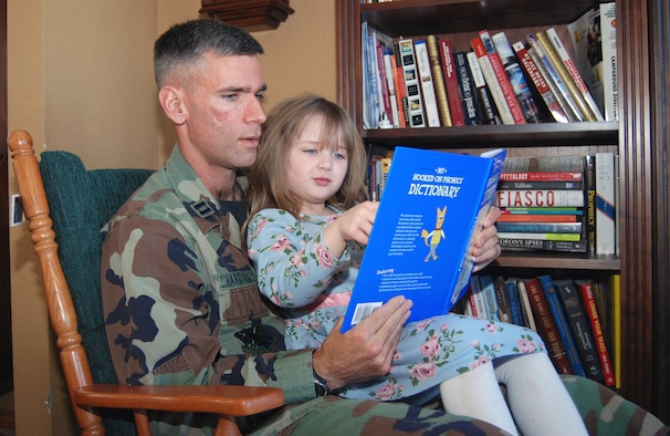 Capt. Daniel Harding, from the 544th Intelligence Group, reads with his 5-year-old daughter in his home in Colorado Springs.