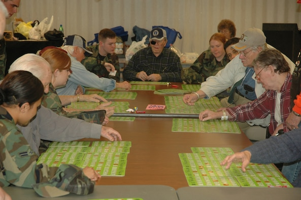 Students from the First Term Airmen Center aid residents from Sim's Veteran Home while playing bingo on Valentines Day.  To help with the veteran's hand-eye coordination, the Airmen repeat the number and point out numbers missed by the residents. (U.S. photo by Airman 1st Class Anthony J. Hyatt)