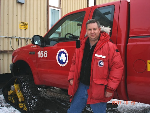 Master Sgt. Kirk Babcock stands beside one of the many specially outfitted trucks used to transport those stationed at McMurdo Station, Antarctica. Note the track used for front wheels.