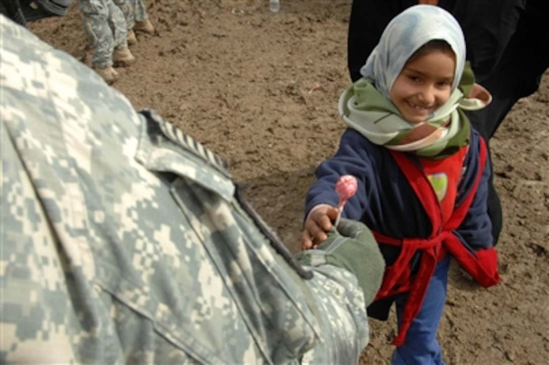 A U S  Army soldier gives an Iraqi girl a lollipop