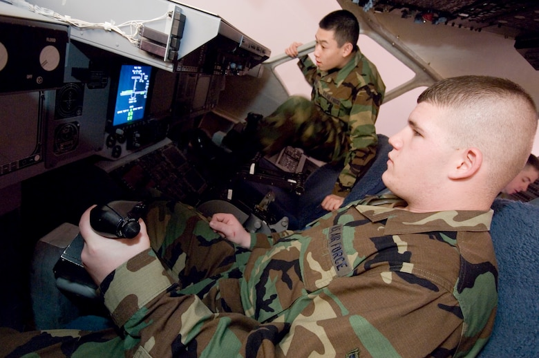Airman Basic Timothy Brammer, right, seated in the cockpit of a C-17 flight control trainer, learns to operate the flight controls during a recent class while Airman Basic Nicholas Tran slips into his seat to await his turn. The Airmen are going through training before being assigned to a base. (All photos by Abner Guzman.)
