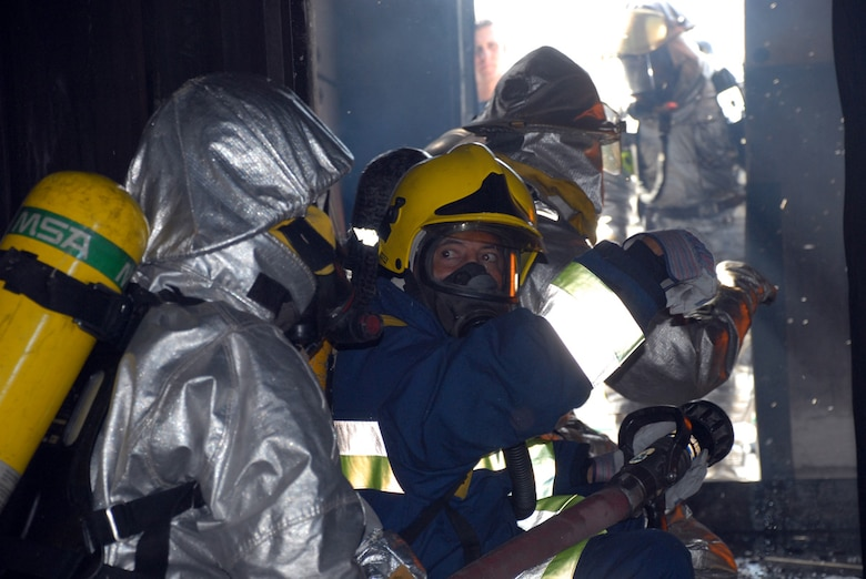 A civilian Honduran firefighter looks for the OK signal before pushing into a fire engulfed room at the Joint Task Force-Bravo ?burn house,? a two-level training structure constructed of concrete and metal. The firefighters are participating in a JTF-Bravo-sponsored firefighting subject matter expert exchange. To make the experience of entering a burning building as realistic as possible, firefighters start a controlled fire burning inside the structure which provides a smoky atmosphere and temperatures of 900 degrees at the fire?s base and 1400 at the ceiling. (U.S. Air Force photo by Tech. Sgt William Farrow)