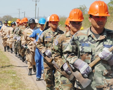 Honduran military and civilian firefighters march toward an area of Soto Cano Air Base to dig a fire break (a gap in vegetation or other combustible material that is expected to slow or stop the progress of a wildfire). The firefighters participated in a JTF-Bravo-sponsored firefighting subject matter expert exchange, a learning exposition for firefighters.  During the exchange, a great level of importance is placed on land navigation and fighting wildfires. (U.S. Air Force photo by Tech. Sgt William Farrow)