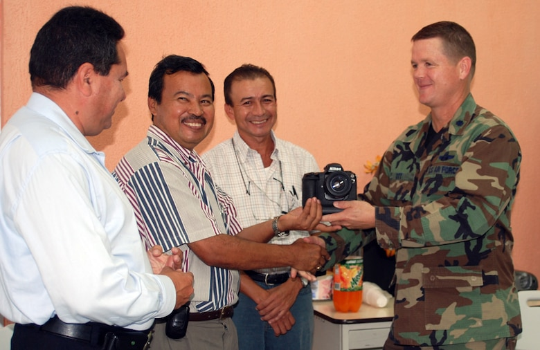 Air Force Lt. Col. Lawrence Ott, Joint Task Force-Bravo deputy commander delivers an assortment of cameras and lenses to journalism department staff members Jose Gomez, Julio Cesar Turcios and Ildefonso Marcia at Universitario Regional del Centro, Comayagua, Honduras. The equipment was made available using a Defense Reutilization and Marketing Service program.