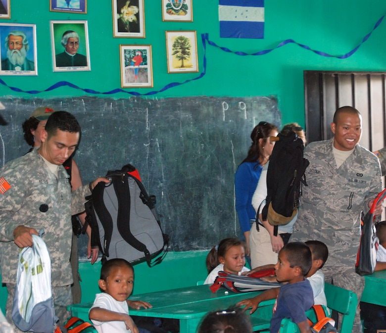 Army Sgt. 1st Class Julio Reyes and Air Force Staff Sgt. Matthew Delgado, from Joint Task Force Bravo, give backpacks with school supplies to children at a school in Humuya, Honduras. The backpacks were donated by children in the United States through the Give a Kid a Backpack organization in Florida.  (U.S. Air Force photo by Tech. Sgt John Asselin)