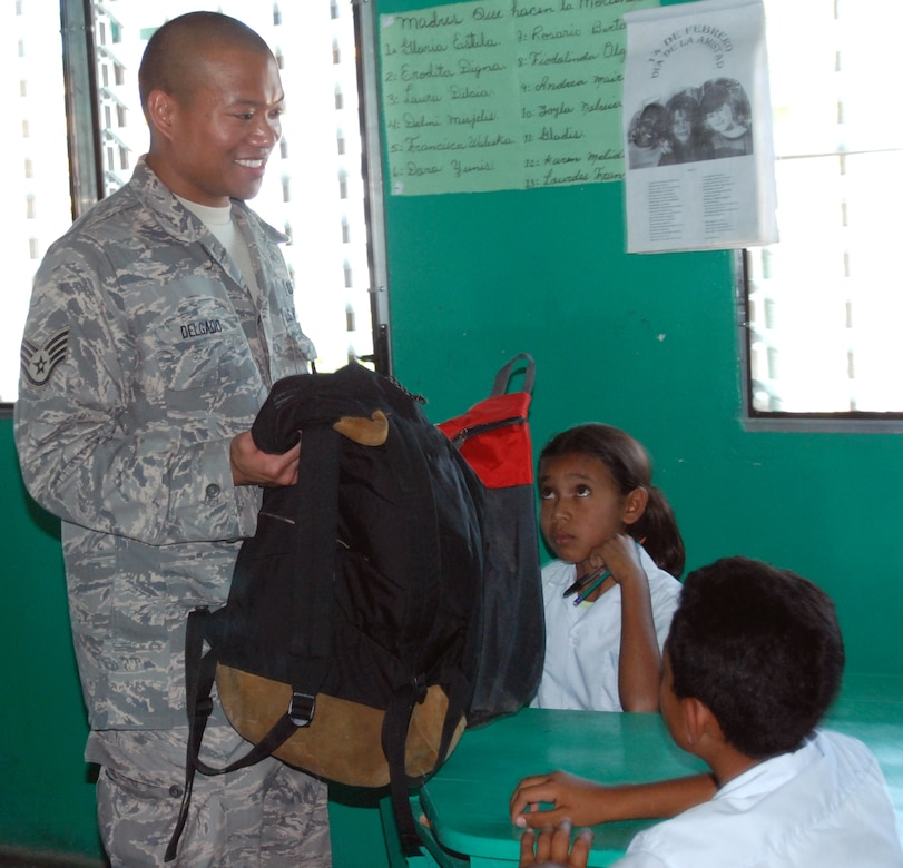 Air Force Staff Sgt. Matthew Delgado, a JTF-Bravo Joint Operations Center controller, give backpacks packed with school supplies to children at a school in Humuya, Honduras. Five representatives from the Give a Kid a Backpack organization in Florida and 15 volunteers from JTF-Bravo distributed more than 700 backpacks packed with school supplies to children at five schools and two orphanages in the Comayagua and La Paz districts. (U.S. Air Force photo by Tech. Sgt John Asselin)