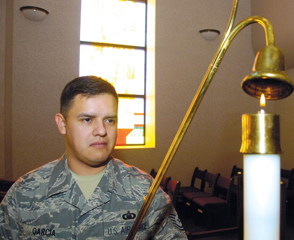 Tech. Sgt. Jason Garcia snuffs out a candle in the main sanctuary after catholic mass services held at Chapel One on Feb. 18. Sergeant Garcia is the 316th Wing Chapel One Readiness NCOIC. (US Air Force/Bobby Jones)