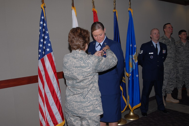 Col. Merrily Madero, 17th Training Wing vice commander, pins a fire protection badge on Airman Basic Jessica Morehouse during a special graduation ceremony Feb. 14. (U.S. Air Force photo by Staff Sgt. Angela Malek)