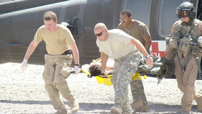 Staff Sgt. Chris Boykins helps unload a MEDEVAC patient in the Central Command's area of responsibility.  (Courtesy photo)