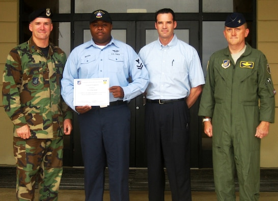 Aviation Support Equipment Technician Second Class Willie L. Ratliff is presented with the Vigilant Warrior certificate by (from left) Lt. Col. Erik Goepner, 36th Security Forces Squadron, Maj. William Wehner, AFOSI Detachment 602 acting commander, and Col. Gregory Cain, 36th Wing vice commander. AS2 Ratliff was awarded the honor after reporting suspicious individuals filming unauthorized footage of the flight line on Feb. 12 in a Vigilant Warrior scenario. (Courtesy photo)
