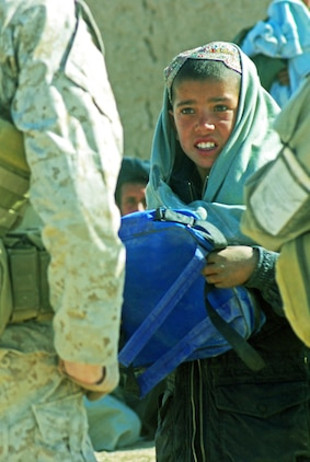 An Afghan boy receives a school bag from Afghan National Army soldiers and a Marine Special Operations Company's team members. The ANA and MSOC unit were visiting a Helmand Province village in late February. Photo by Marine Staff Sgt. Luis P. Valdespino Jr.