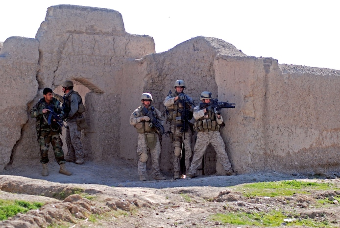 Marines with a Marine Special Operations Company and an Afghan National Army soldier position themselves to fight Taliban fighters who attacked them a few minutes prior. ANA soldiers and MSOC Marines were visiting the southern Afghanistan village when they were attacked by Taliban fighters in late February. Photo by Marine Staff Sgt. Luis P. Valdespino Jr.