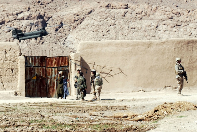 Marines with a Marine Special Operations Company secure an area of a Helmand Province village in which they were under attack by Taliban fighters, while a Chinook CH-47 pulls in to provide support for the Marines. Afghan National Army soldiers and MSOC Marines were visiting the southern Afghanistan village when they were attacked by Taliban fighters in late February. Photo by Marine Staff Sgt. Luis P. Valdespino Jr.