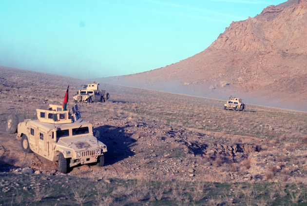 A Marine Special Operations Company's Humvees traverse through mountainous terrain in Helmand Province after a day of battling against Taliban fighters in a southern Afghanistan village. Photo by Marine Staff Sgt. Luis P. Valdespino Jr.
