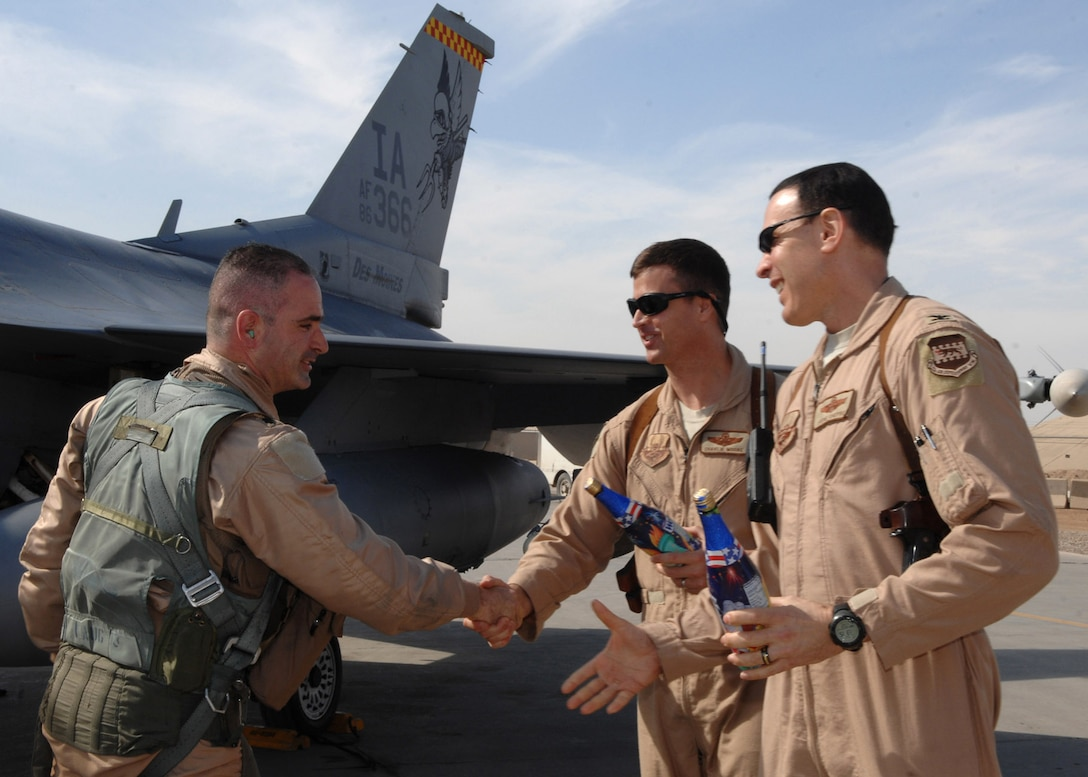Lt. Col. George Uribe is greeted and congratulated by Col. Steven Shepro and Col. Charles Moore after completing 1,000 combat flying hours as an F-16 Fighting Falcon pilot Feb. 17 at Balad Air Base, Iraq. Colonel Uribe is a 332nd Expeditionary Operations Group fighter pilot and deployed from Tyndall Air Force Base, Fla. Colonel Shepro is the 332nd Air Expeditionary Wing vice commander, and Colonel Moore is the 332nd Expeditionary Operations Group commander. (U.S. Air Force photo/Senior Airman Julianne Showalter)