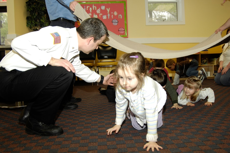 HANSCOM AFB, Mass. – Robert Coonce (left), Hanscom Fire Prevention Services and assistant fire chief, guides Elena Weissman (right) and other children from the Hanscom School Age program through a drop and crawl drill designed to teach children how to safely get out of a smoke-filled house. The interactive exercise was part of a new Juvenile Fire Setters program that the Fire Department unveiled Feb. 26. (U.S. Air Force photo by Linda LaBonte Britt)