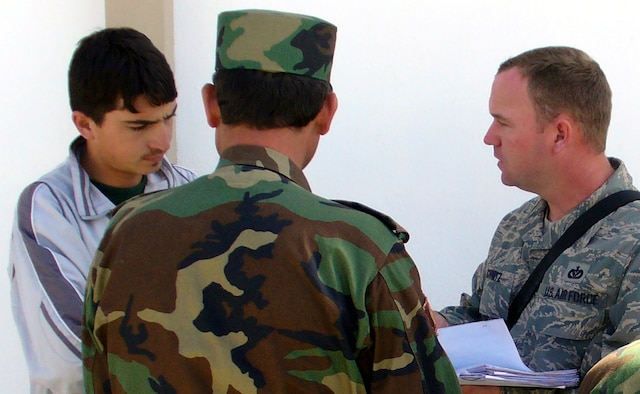 Tech. Sgt. Samuel Schmitz (right), contingency skills instructor from the U.S. Air Force Expeditionary Center's 421st Combat Training Squadron at Fort Dix, N.J., talks with an Afghan National Army soldier through an interpreter in a village near Kabul, Afghanistan, Sept. 29, 2007 during his deployment there.  Sergeant Schmitz, an Air Force civil engineering power production specialist, deployed as an Afghan National Army Central Movement Agency Mentor from January 2007 to February 2008.  (U.S. Air Force Photo)