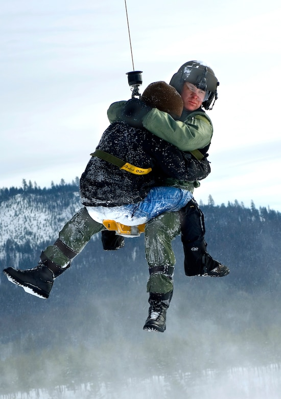 "Riding the rescue hoist back to the UH-1N Huey helicopter, Staff Sgt. Weiss secures a ""patient"" during rescue training. He had to do a similar extraction with an avalanche victim recently. (Air Force photo by Tech. Sgt. Matthew Hannen)"