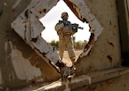 A U.S. Army soldier stands outside the front gate of a house he has just searched during a clearing operation in Kesra, Iraq, Feb. 24, 2008.