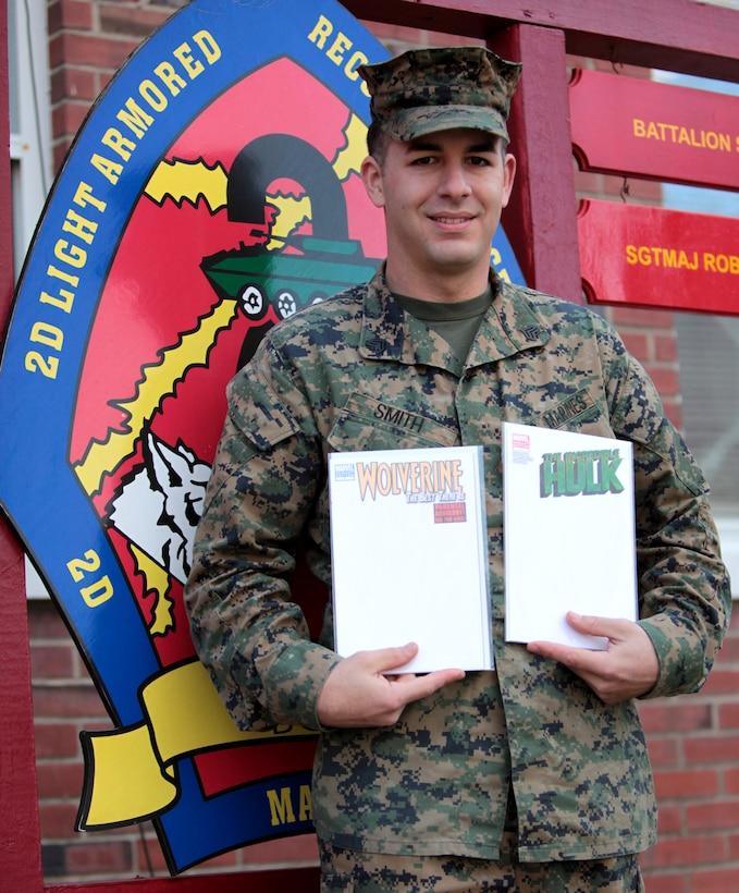 Sgt. Jacob Smith, a scout squad leader with Headquarters and Service Company, 2nd Light Armored Reconnaissance Battalion and founder of Comics 4 Heroes, poses holding white covered Marvel Comic books in front of the LAR Battalion sign aboard Marine Corps Base Camp Lejeune, N.C., Dec. 19. Depending on how well the auction goes, Smith says he would like to make Comics 4 Heroes a yearly event.