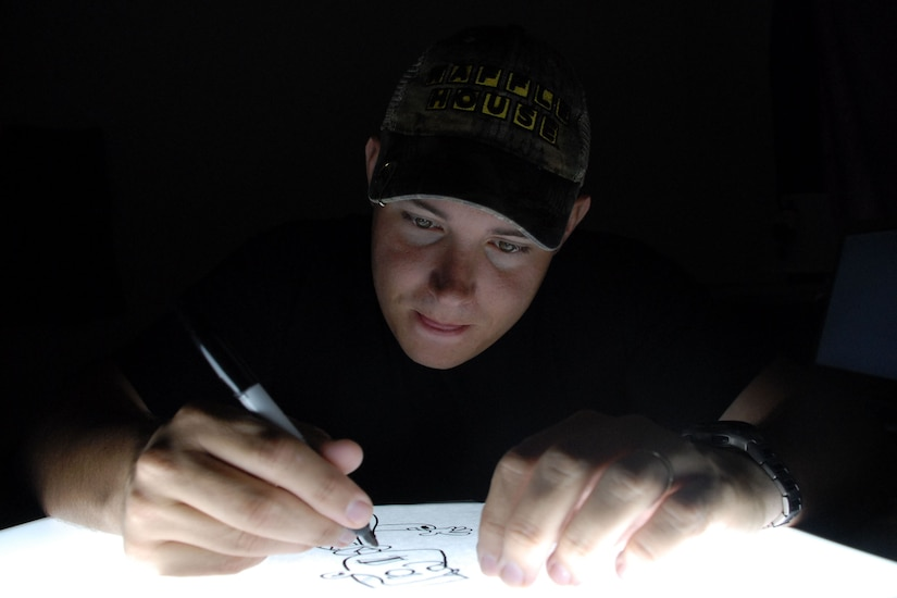 SOTO CANO AIR BASE, Honduras - Staff Sgt. Austin M. May, a Public Affairs noncommissioned officer deployed here from Laughlin Air Force Base, Texas, works on a character from his comic strip, Air Force Blues.  Sergeant May recently published a book of his comics, and Air Force Blues is slated to appear in an upcoming issue of Airman Magazine. (U.S. Air Force photo by Tech. Sgt. Sonny Cohrs)